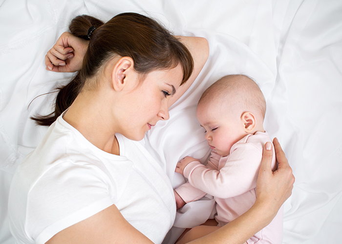お母さんが横たわって、赤ちゃんを抱き寄せながら見つめている写真|不妊治療HP
