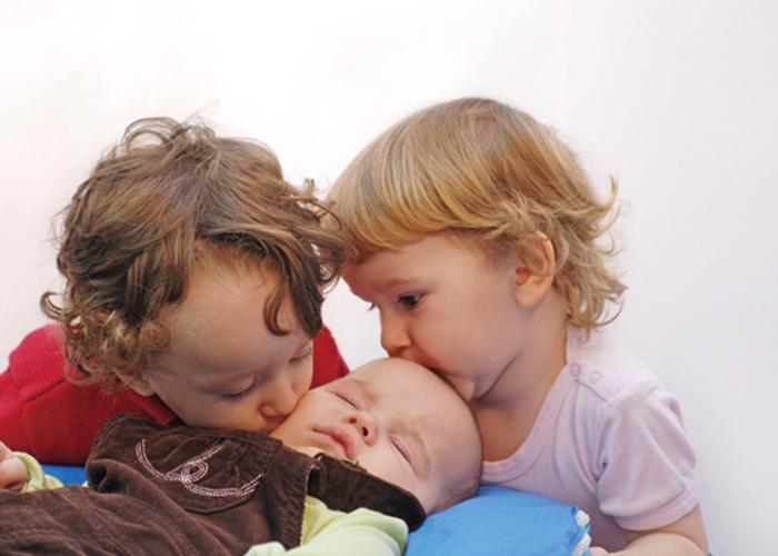 二人の子どもが赤ちゃんにキスしている写真|不妊治療HP