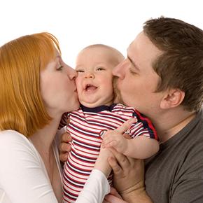 お父さんとお母さんが左右から可愛い赤ちゃんの頬にキスしているところ|不妊治療HP