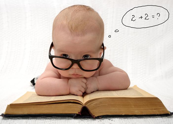 黒縁のメガネをかけて分厚い本の上で頬杖をつく赤ちゃん|不妊治療HP
