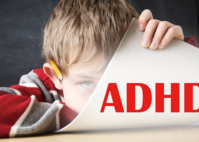 ADHDと書いた紙をめくっている気難しそうな男の子|不妊治療HP