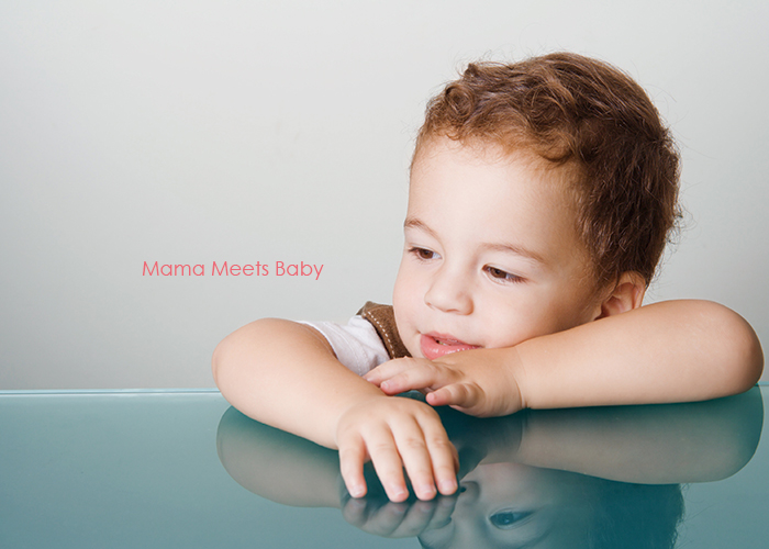 大きなテーブルに肘をついて何かを見つめる可愛い子ども|不妊治療HP