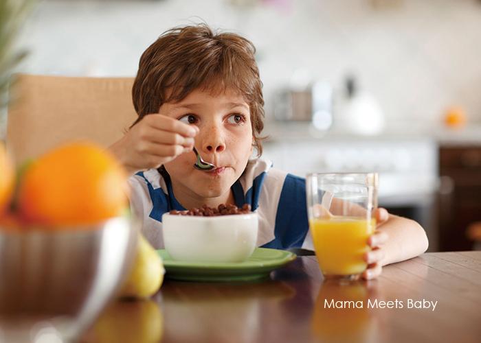 オレンジジュース片手にシリアルを頬張る少年|不妊治療HP