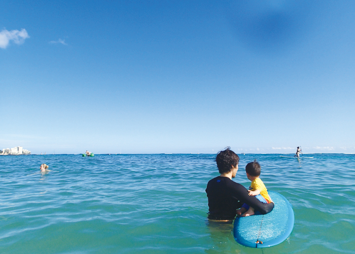 ハワイの海でサーフボードに座っている子供|不妊・マタニティHP
